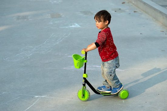 child riding scooter outdoors