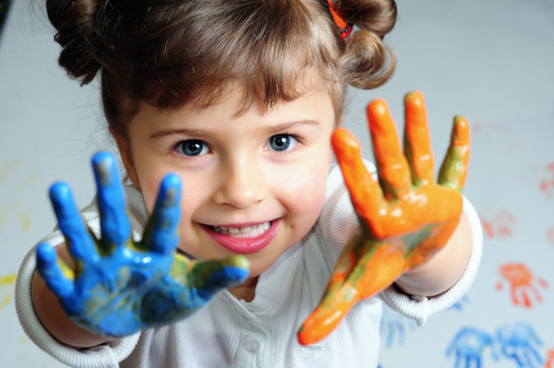 child with color paint on both hands