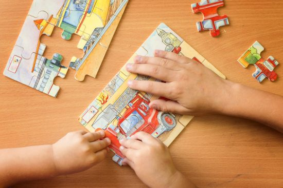 Children Assembling Small Jigsaw Puzzles